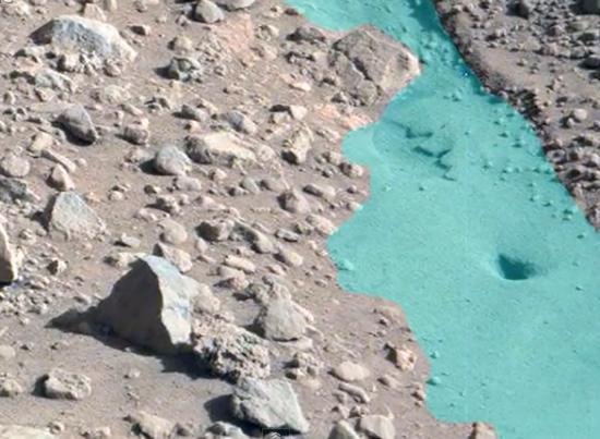 Seria esta uma possível evidência de uma nascente d'água na superfície marciana?  (A área foi delineada em azul para melhor vizualização.)