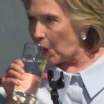 Hillary Clinton 'ejeta' corpos estranhos em copo d'água; Internet a acusa de ser reptiliana